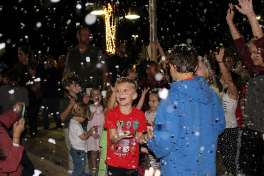 "The crowd enjoys ""snow"" during the 2018 Christmas Tree Lighting."