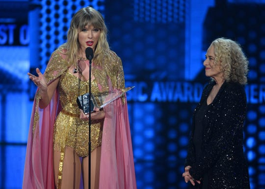 Taylor Swift, left, accepts the award for artist of the decade at the American Music Awards on Sunday, Nov. 24, 2019, at the Microsoft Theater in Los Angeles. Looking on at right is Carole King.