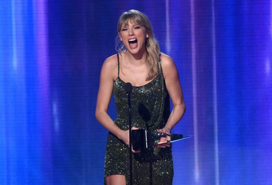 """Taylor Swift accepts the award for favorite pop/rock album for """"Lover"""" at the American Music Awards on Nov. 24, 2019, at the Microsoft Theater in Los Angeles."""