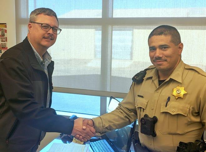 Luna County Sheriff Kelly Gannaway (left) congratulates Deputy Patrol Sergeant Robert Ramirez.
