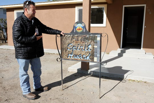 Aztec Code Compliance Officer Andrew DiCamillo places the Aztec Spirit Award sign in front of a renovated house that previously was known as one of the city's problem properties.
