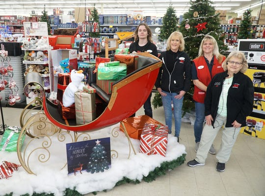 Some staff of South Lyon's Great Lakes Ace Hardware store gather around an original sleigh from a Hudsons' Christmas display - that's on loan to the shop through Christmas. From left are Andrew Ganss, Cindy Heins, Teresa Winekoff, and Sue Zimmerman.