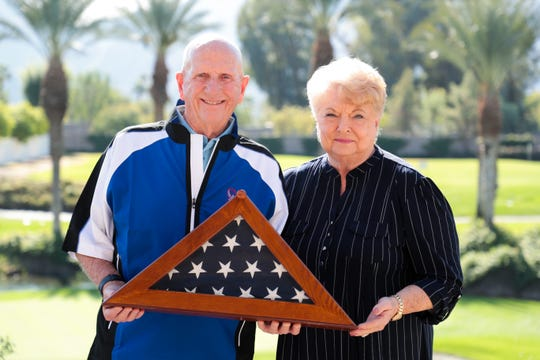 Walt and Judy Van Benthuysen, founders of American Friends of Our Armed Forces and organizers of the local Adopt-A-Marine Program stand with an American flag on the patio of their home in Indian Wells, Calif. on Monday, November 25, 2019.