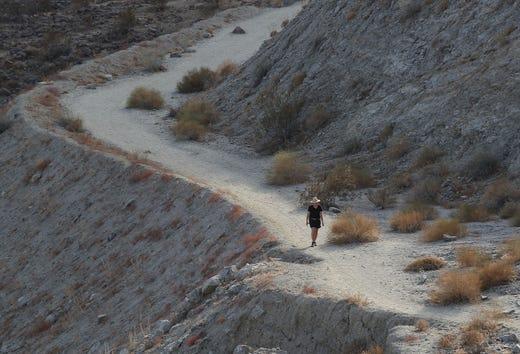 A hiker walks the Bump and Grind Trail near Palm Desert, November 15, 2019.