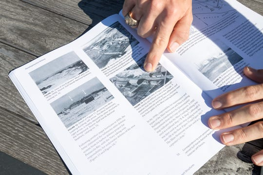 Brent Everitt, public affairs specialist at Gulf Islands National Seashore, points out the mine loading building in a historic photo of Fort Pickens. The building is in the first phase of a three-phase restoration project.