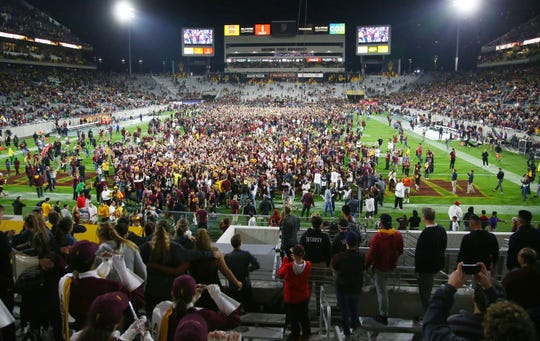 Fans rush the field after Arizona State defeated Oregon on Saturday night at Sun Devil Stadium. ASU became bowl eligible with the victory.