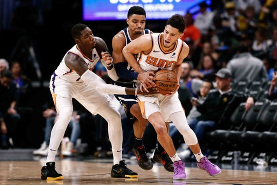 Phoenix Suns guard Devin Booker (1) controls the ball under pressure from Denver Nuggets guard Gary Harris (14) as forward Cheick Diallo (14) screens in the third quarter at the Pepsi Center.