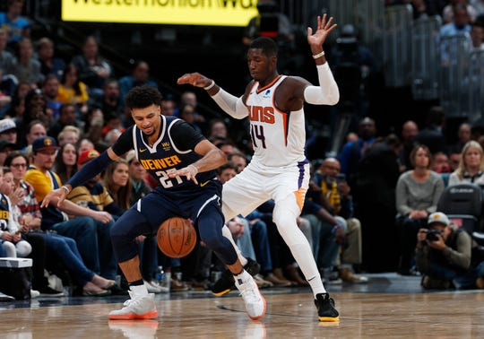 Denver Nuggets guard Jamal Murray, left, reaxches out for a loose ball as Phoenix Suns forward Cheick Diallo defends in the second half of an NBA basketball game Sunday, Nov. 24, 2019, in Denver. The Nuggets won 116-104. (AP Photo/David Zalubowski)