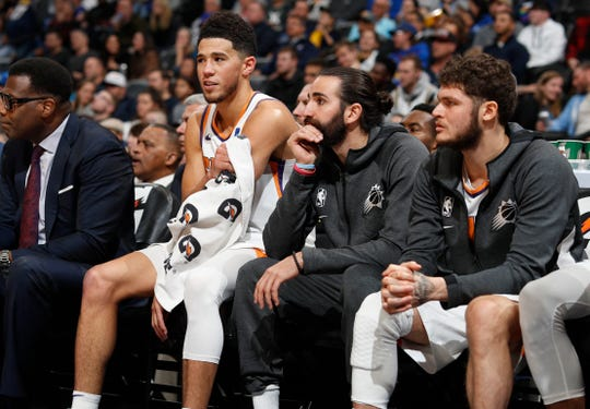 From left, Phoenix Suns guards Devin Booker, Ricky Rubio and Tyler Johnson look on from the bench as time runs out in the second half of an NBA basketball game against the Denver Nuggets, Sunday, Nov. 24, 2019, in Denver. The Nuggets won 116-104. (AP Photo/David Zalubowski)