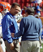 Coaching legends Urban Meyer, left, and Joe Paterno meet before the 2011 Outback Bowl. This was Meyer's last game at Florida before his first retirement from coaching. It also would be Paterno's last bowl game at Penn State. (AP Photo/Chris O'Meara)
