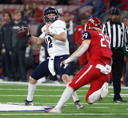 Nevada quarterback Carson Strong passes downfield as Fresno State linebacker Justin Rice closes in during the second half of an NCAA college football game in Fresno, Calif., Saturday, Nov. 23, 2019.