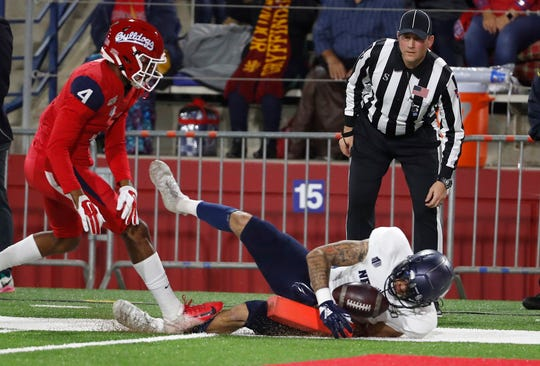 Nevada wide receiver Elijah Cooks dives in for a touchdown as Fresno State defensive back Wylan Free gives chase during the first half of an NCAA college football game in Fresno, Calif., Saturday, Nov. 23, 2019.