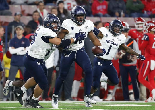 Nevada linebacker Maliek Broady, left, and linebacker Lawson Hall celebrate his interception against Fresno State during the second half of an NCAA college football game in Fresno, Calif., Saturday, Nov. 23, 2019.