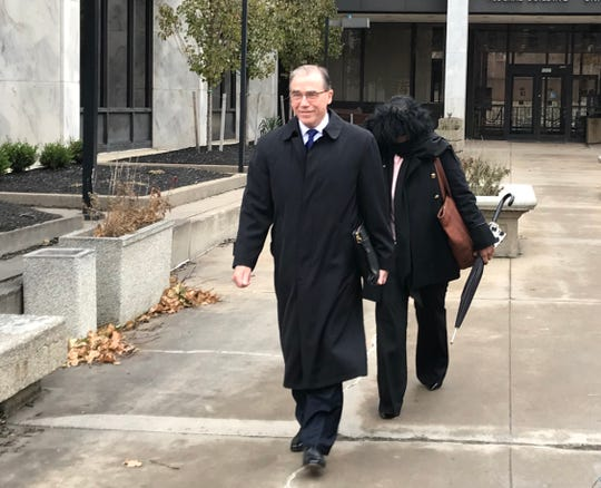 Michael Tallon (front), the attorney for RHA executive secretary Janis White (back) leaves federal court on Monday, Nov. 25, 2019, as Tallon and White attempt to shield her face from television cameras.