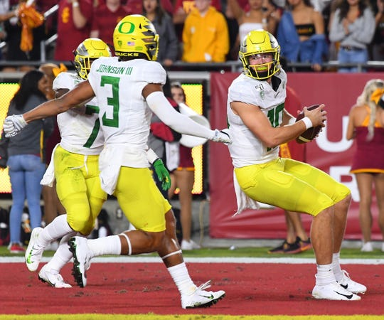 Nov 2, 2019; Los Angeles, CA, USA; Oregon Ducks quarterback Justin Herbert (10) celebrates with wide receiver Johnny Johnson III (3) and running back CJ Verdell (7) after scoring a down in the first half at the Los Angeles Memorial Coliseum. Mandatory Credit: Jayne Kamin-Oncea-USA TODAY Sports