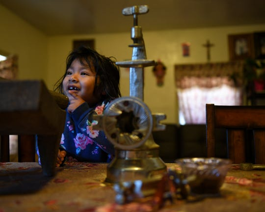Catarina Olea Gomez and Agustin Rodriguez's youngest daughter sits in the kitchen table that's filled with the cooking tools used to make the famous Oaxacan Mole. She watches her mom cook breakfast for the family on Nov. 23, 2019.
