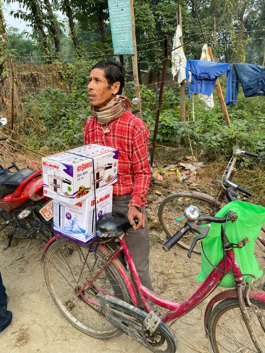A Nepalese man accepts the gift of a water filter and rice cooker from the Terry Mikesa Foundation recently. Terry Mikeska and his sister, Rebekah Ocker, are spending Thanksgiving in the Himalayan nation.