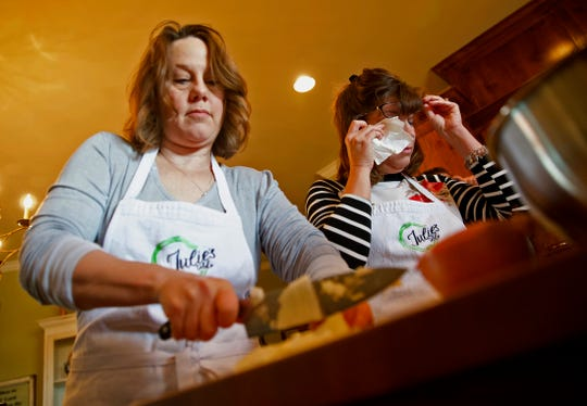 Amy Watkins, left, and Angela Taylor, right, cut onions during a Julie's Table cooking class Saturday, Nov. 23, 2019.