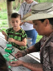 A teacher at the Pemayetv Emahakv Charter School in Florida demonstrates Native American carving techniques to a student as part of a curriculum that mixes both cultural and academic education. Bars of soap are used in the early carving lessons to make it easier for children.