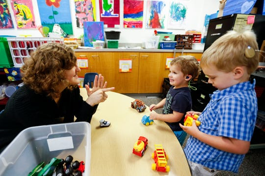 Veronica Halter, a student clinician at Missouri State's preschool for deaf and hard of hearing children, signs to students as they play during class on October 1, 2019.
