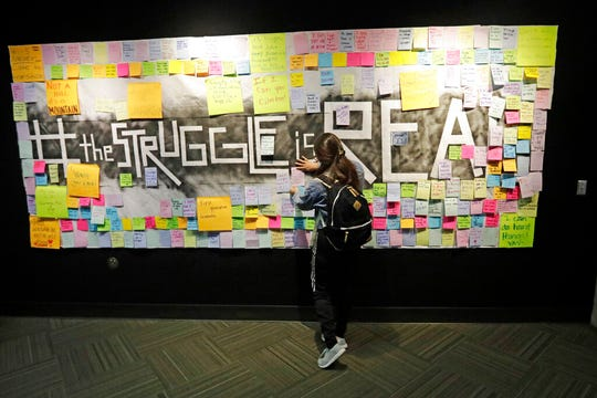 In this Nov. 14, 2019, photo, a student attaches a note to the Resilience Project board on the campus of Utah Valley University, in Orem, Utah. The purpose of the project is to let students know that it is OK to struggle. More college students are turning to their schools for help with anxiety, depression and other mental health problems. That's according to an Associated Press review of more than three dozen public universities. (AP Photo/Rick Bowmer)