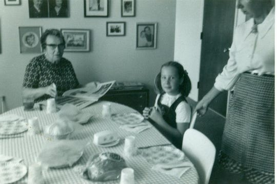Eight-year-old Cynthia Carr is seated at the family dinner table with her grandmother, Vera Carr. Cynthia's mother, Mary Carr, is standing.