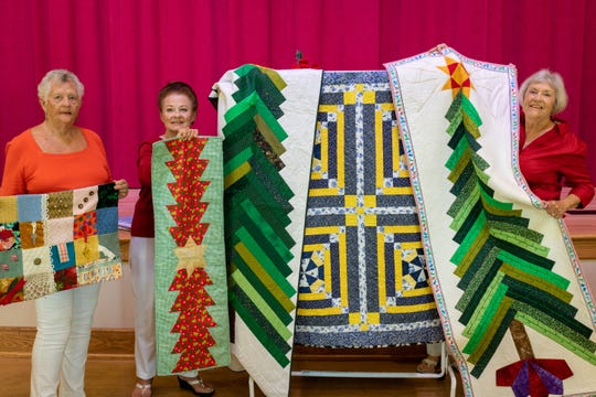 """Pat Wempe, left, displays a handmade """"fidget quilt"""" for Alzheimer's patients, while Maggie Fleming and Frances Archibald showcase other beautiful quilts – one of which will be raffled off – at the Dec. 7 Christmas Tree Lane, the holiday boutique and cookie/bake sale at First Presbyterian Church of Vero Beach."""
