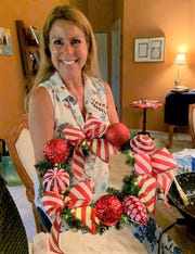 Maria Reich displays a wreath centerpiece she made for the Dec. 9 Christmas Cookie Luncheon benefiting Caring Children Clothing Children. The event is at Mariner Sands Country Club in Stuart.