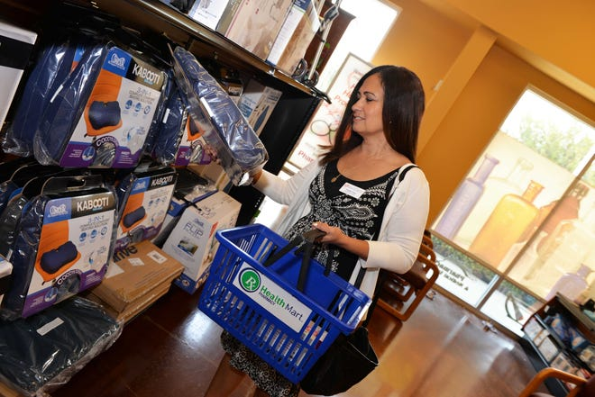 Treasure Coast Urgent Care's Yvette Cruz fills her basket full of goodies during the 2018 kickoff event for Holiday Angels Gift Drive for senior citizens.