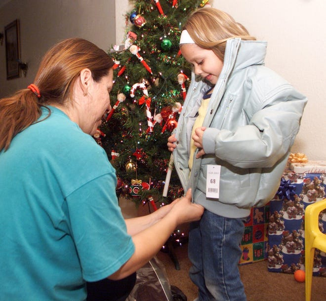 Carment Garcia helps her 5-year-old daughter, Cassandra, put on her new coat courtesy of Operation Noel.