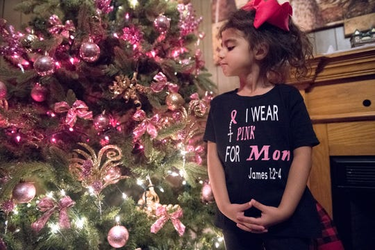 5-year-old Izalyn Rivera, daughter of cancer patient Luz Rivera, stands by her family's Christmas tree in their Vineland home.  The family was selected for the Salvation Army Adopt-A-Family showcase, which will kickstart a campaign to help link 200 families in need with benefactors.