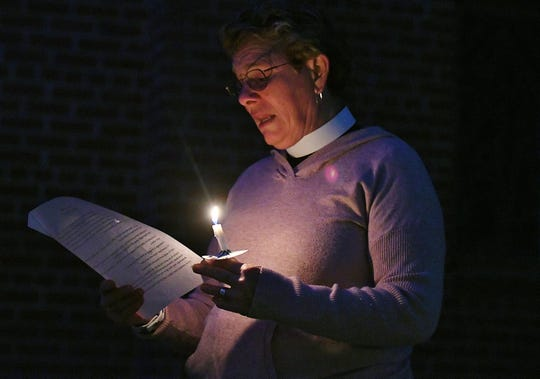 Pastor Suzy Ward leads a prayer during candlelight vigil commemorating the Transgender Day of Remembrance at St. Paul's Episcopal Church on Nov. 24, 2019.