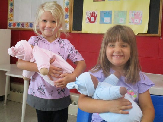 Students hold two of the four dolls that D.C. Everest 4K Teacher Teri Eberhardy purchased for her classroom at St. John's Lutheran School, Wausau, at the beginning of this school year. Eberhardy was awarded a grant from the D.C. Everest Foundation, which allowed her to purchase the dolls.