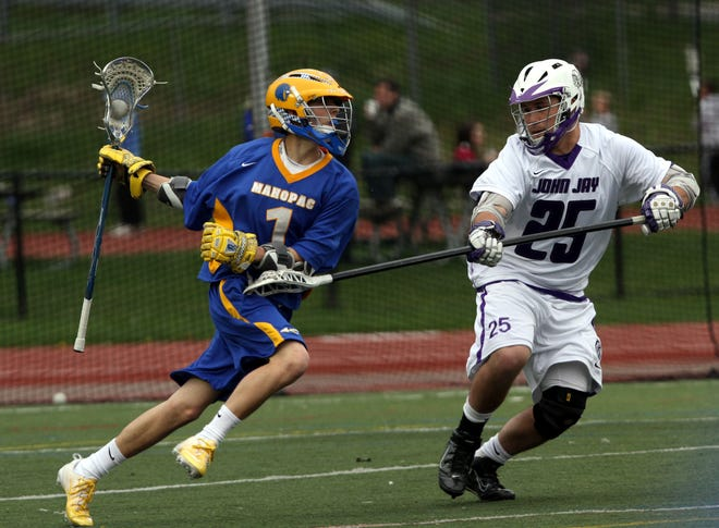 From left, Mahopac's Jon Bota (1) tries to get around John Jay's Brian Kass (25) during a boys lacrosse game at John Jay High School in Cross River May 2, 2011.