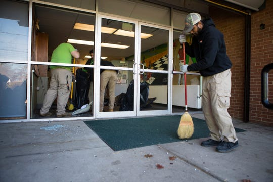 A crew from SERVPRO Restoration Services replaces the front entrance windows at Kingswood Community Center Monday morning after the windows were struck by gunfire in a double shooting Saturday night in Wilmington.