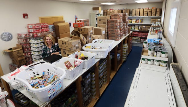 Jaime Trout, executive director of Eastside Community Ministries, stands in the organization's food pantry. Area food pantries are seeking proteins as more people are turning to pantries for help. The food shown here will only carry Eastide through a couple of weeks.