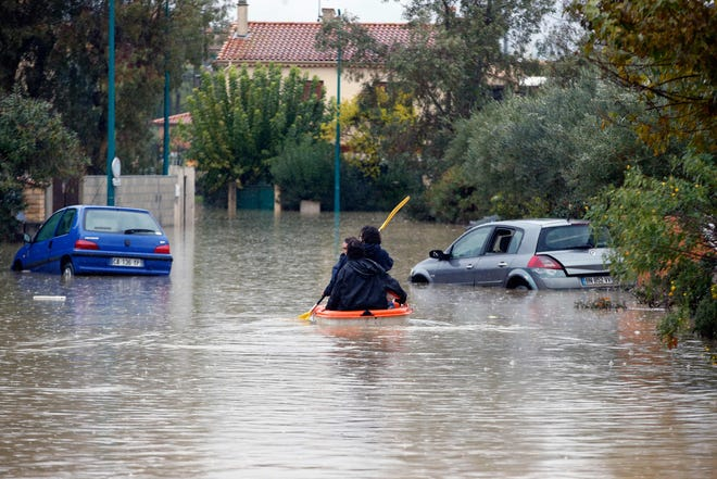 People ride on a small boat next to partially submerged cars on a flooded street after heavy rains in Le Muy, southeastern France, on November 24, 2019.