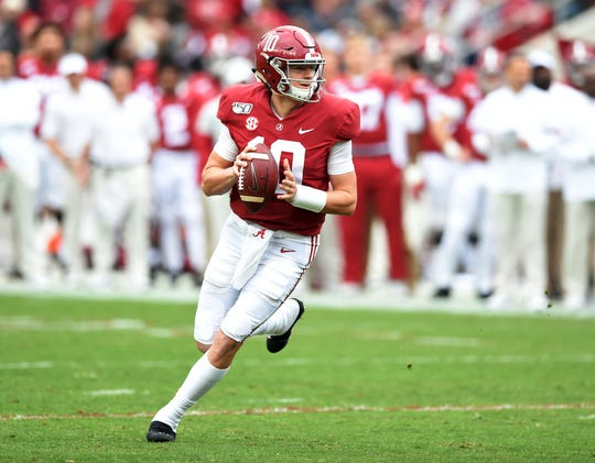 Alabama quarterback Mac Jones rolls out to pass against Western Carolina during the second quarter at Bryant-Denny Stadium.