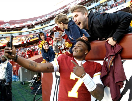 Washington Redskins quarterback Dwayne Haskins takes selfies with fans at the end of the win against the Detroit Lions.