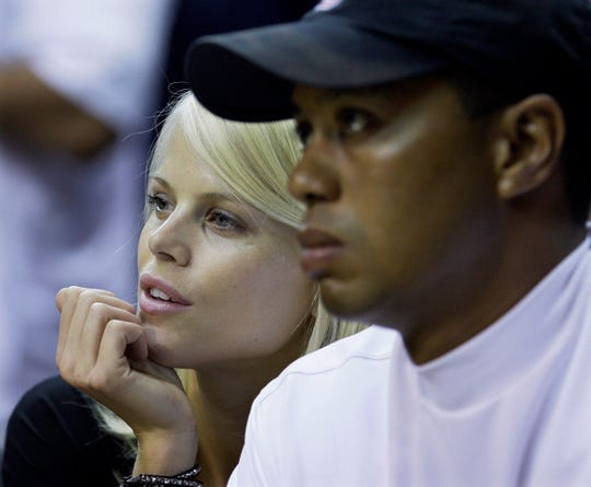 In this June 11, 2009 file photo, Elin Nordegren and then-husband Tiger Woods attend Game 4 of the NBA Finals.