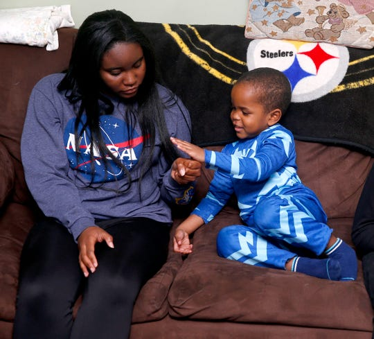 Yazz, 15, and her brother Makhi, 3, play on the couch at their Howell home Monday, November 25, 2019.  Sonya Middleton recently adopted them, along with their brother Eric, 11, and sister Ahdina, 8.