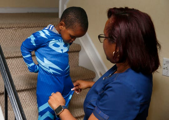 Sonya Middleton helps her son Makhi, 3, with his pajamas in their Howell home Monday, November 25, 2019.  Middleton recently adopted the boy and his siblings Ahdina, 8; Eric, 11; and Yazz, 15.