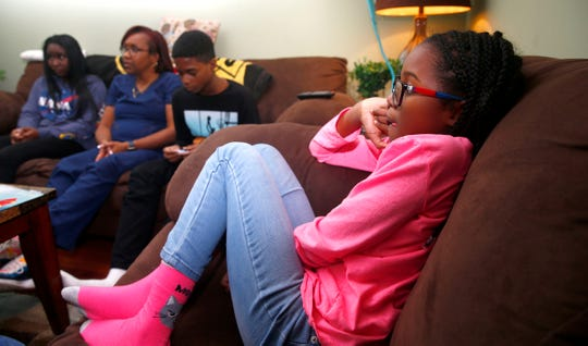 Ahdina, 8, listens as her mother Sonya Middleton is interviewed along with sister Yazz, 15, and brother Eric, 11, in the Howell home Monday, November 25, 2019 Middleton recently adopted the siblings along with their brother Makhi, 3.