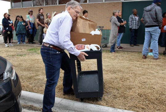 Volunteer Bill Rister negotiates the curb after pushing a cart with a Thanksgiving dinner to car outside First Central Presbyterian Church's food pantry on Tuesday. Complete meals were being given away, an example of both Abilene's generosity and volunteerism.  Nov. 26 2019