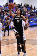 Abilene High's Justine Martinez (12) goes into the air for a layup against Cooper at Cougar Gym on Monday. The Lady Cougars won 62-37.