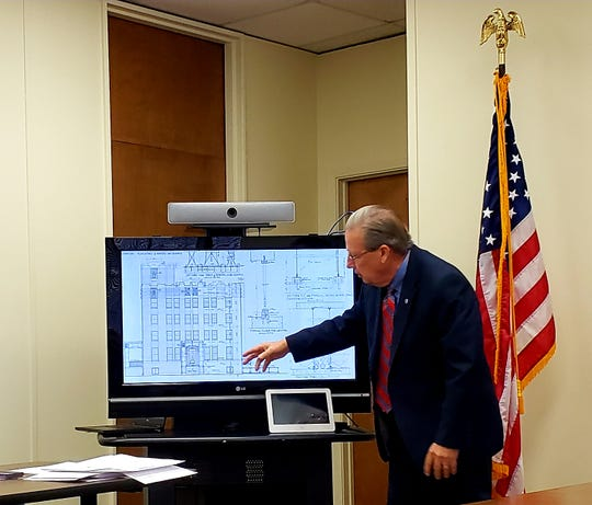 County Judge Downing Bolls shows original plans for the former Taylor County Jail on Pecan, designed by architect David Castle.