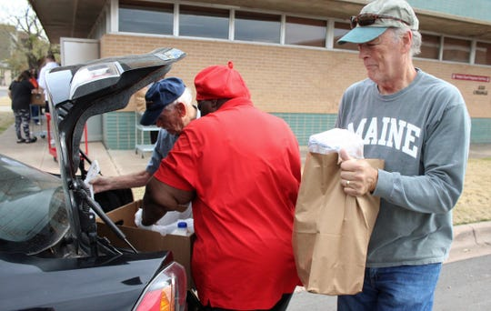 John Powell, right, readies to place a bag of groceries in the trunk of Guinevere Evans' car Tuesday after outside First Central Presbyterian Church's food pantry on Orange Street. The church was providing 150 complete meals to families for Thanksgiving.