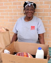 Linda Nicholson waits for her ride after getting her Thanksgiving meal Tuesday at First Central Presbyterian Church's food pantry. She was appreciative of getting to feed four children.