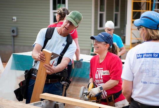Asheville Habitat for Humanity Construction Supervisor John Meadows, left, instructs Keller Williams Team Browne volunteer Natalie Malis. In 2018, 2,350 volunteers collectively donated more than 70,700 hours of service to Asheville Habitat.