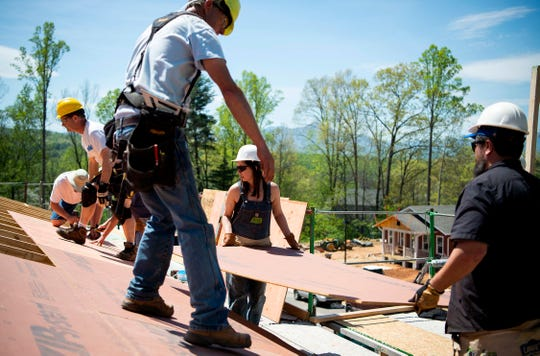 Volunteers from New Morning Gallery work on a Habitat for Humanity home. In 2018, 2,350 volunteers collectively donated more than 70,700 hours of service to Asheville Habitat for Humanity.